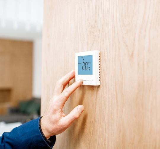 uomo regola termostato casa